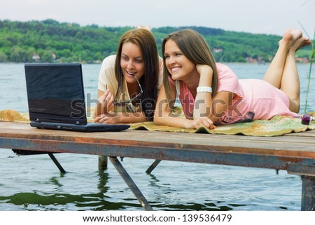 Holidays and internet / Two cheerful young woman use a laptop on holidays - stock photo