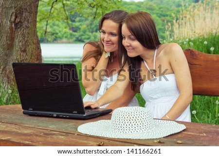 Holidays and Internet / Two young woman are sitting in nature and use theirs laptop to surfing on the internet - stock photo