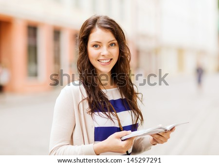 holidays and tourism concept - beautiful girl looking into tourist book in the city - stock photo