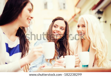 holidays and tourism concept - beautiful girls drinking coffee in cafe - stock photo