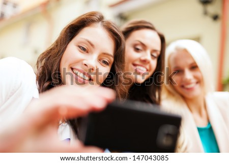 holidays and tourism concept - beautiful girls taking selfie in outdoor cafe in city - stock photo