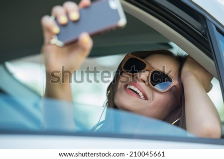 Holidays and tourism concept - smiling teenage girl taking selfie picture with smartphone camera outdoors in car - stock photo