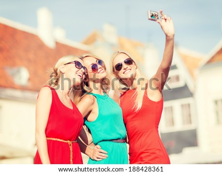 holidays and tourism, modern technology concept - beautiful girls taking picture in the city - stock photo
