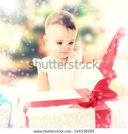 Holidays, baby girl opening box with presents, christmas, birthday, new year, x-mas concept - happy child girl with gift boxes  - stock photo