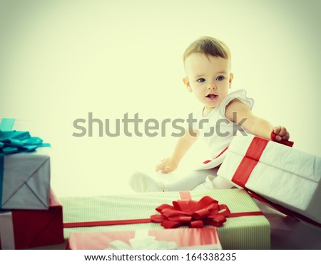 Holidays, baby girl with presents, christmas, birthday, new year, x-mas concept - happy child girl with gift boxes, toned - stock photo