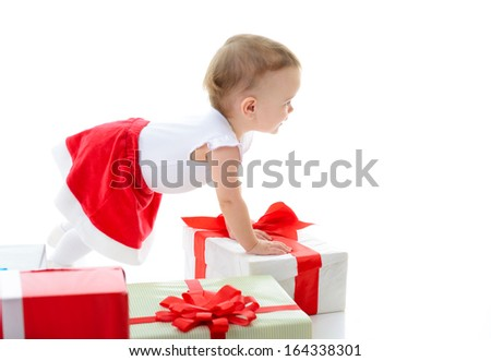 Holidays, baby girl with presents looking at copyspace, christmas, birthday, new year, x-mas concept - happy child girl with gift boxes, over white - stock photo