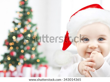 holidays, babyhood, childhood and people concept - happy baby in santa hat over christmas tree lights and gifts background - stock photo