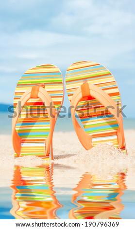 Holidays Background. Beach sandals on the sandy coast - stock photo