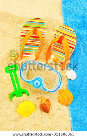 Holidays Background. Seashells and diving mask on the ocean beach - stock photo
