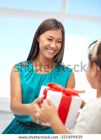holidays, birthday family, childhood and people concept - happy mother giving present to her daughter at home - stock photo