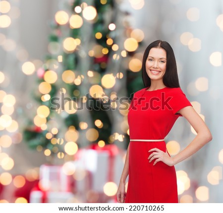 holidays, celebration and people concept - smiling woman in red dress over christmas tree background - stock photo