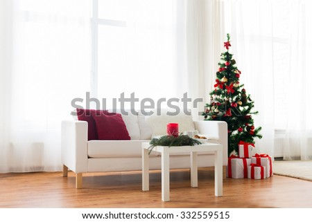 holidays, celebration, decoration and interior concept - sofa, table and christmas tree with gifts at home - stock photo