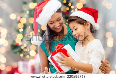 holidays, celebration, family and people concept - happy mother and little girl in santa helper hats with gift box over living room and christmas tree background - stock photo