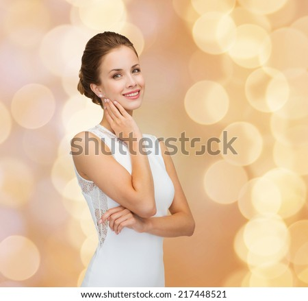 holidays, celebration, wedding and people concept - smiling woman in white dress wearing diamond ring over golden lights background - stock photo