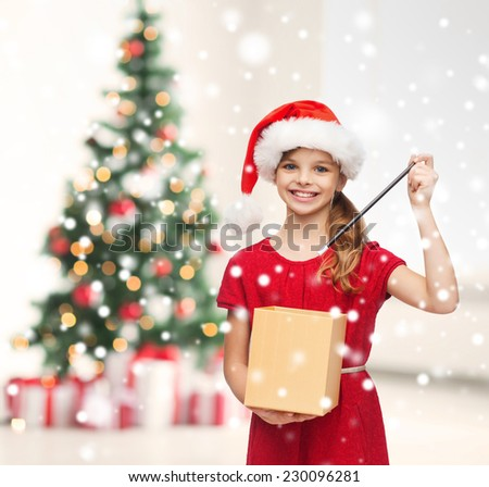 holidays, childhood and people concept - smiling girl in santa helper hat with gift box, magic wand over living room and christmas tree background - stock photo