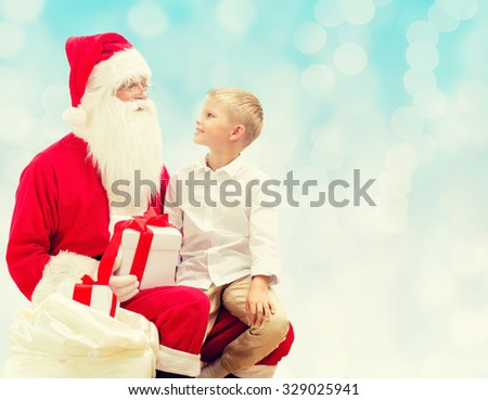 holidays, christmas, childhood and people concept - smiling little boy with santa claus and gifts over blue lights background - stock photo