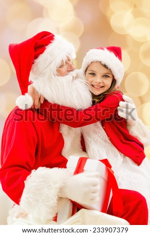 holidays, christmas, childhood and people concept - smiling little girl hugging with santa claus over beige lights background