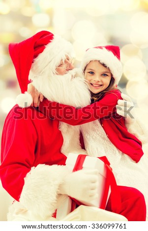 holidays, christmas, childhood and people concept - smiling little girl hugging with santa claus over lights background - stock photo