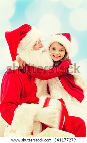holidays, christmas, childhood and people concept - smiling little girl hugging with santa claus over blue lights background - stock photo