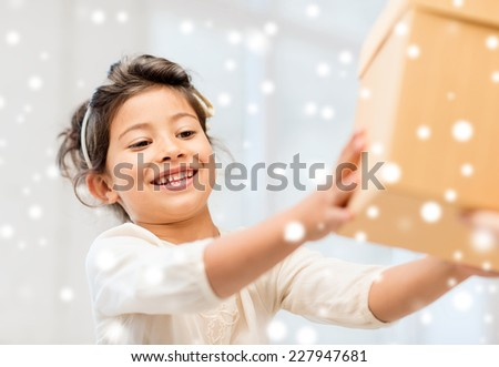 holidays, christmas, childhood and people concept - smiling little girl with gift box at home - stock photo