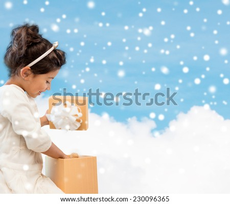 holidays, christmas, childhood and people concept - smiling little girl with gift box over blue snowy sky with cloud background - stock photo
