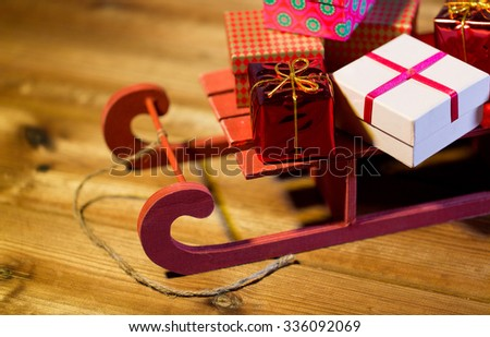 holidays, christmas, presents, new year and celebration concept - close up of many little gift boxes on red wooden sleigh on wooden table - stock photo