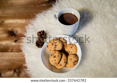 holidays, christmas, winter, food and drinks concept - close up of cups with hot chocolate or cocoa drinks and oat cookies on white fur rug - stock photo