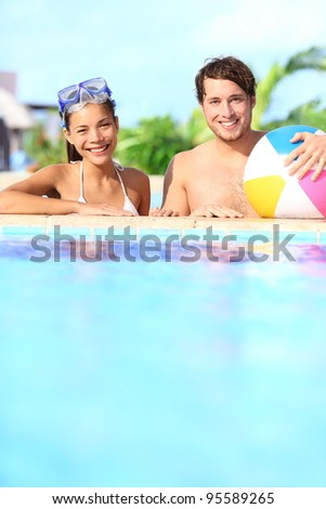 Holidays couple in pool having fun in sunny vacation resort under the sun. Young mixed race couple, Caucasian man, Asian woman. - stock photo