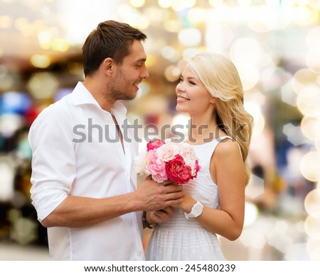 holidays, dating, people and dating concept - happy couple with bunch of flowers over lights background - stock photo