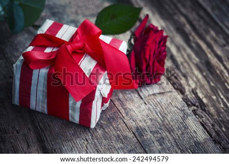 Holidays Decoration with gift box and red rose in vintage color/ holidays background with a present and rose