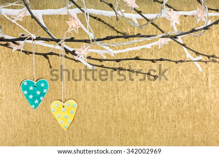holidays decoration with gingerbread and stars christmas lights on tree branch - stock photo