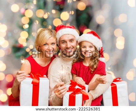 holidays, family and people concept - happy mother, father and little girl in santa helper hats with gift boxes and sparklers over living room and christmas tree background - stock photo