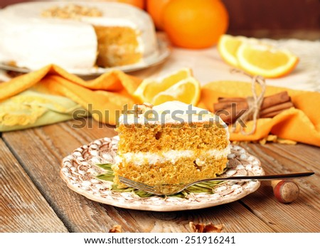 Holidays, food and drink concept. Carrot cake on a wooden table with oranges, nuts and cinnamon. Selective focus - stock photo