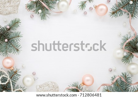 Holidays frame of new year`s decorations on white background. Fir branches, balls, ribbon and pearls, pastel colors