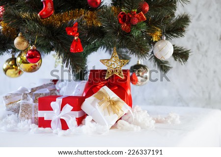 Holidays horizontal background with Christmas fir tree with red,gold and white decoration and cute gift boxes with bows - stock photo