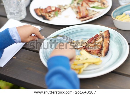 holidays, junk food, dinner, children and people concept - close up of child hands with fork and plate eating pizza at table in summer garden - stock photo