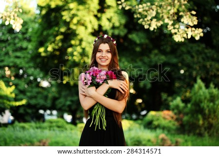 Holidays, love and flowers concept. Outdoors portrait of beautiful young woman with long brunette hair holding bouquet of pink peonies. Fashion model girl with bunch of flowers outdoors in summer, - stock photo
