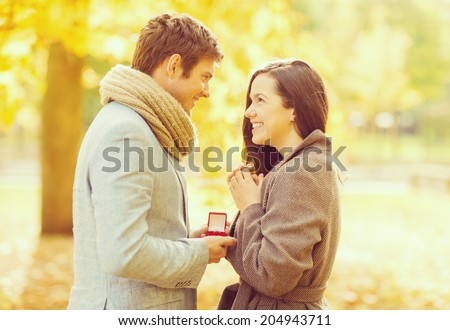 holidays, love, couple, relationship and dating concept - romantic man proposing to a woman in the autumn park - stock photo
