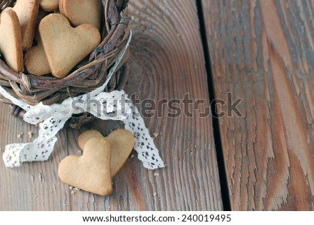 Holidays, love, food and drink concept. Handmade heart cookies for Valentine's day in a basket on a wooden table in a vintage style. Selective focus - stock photo