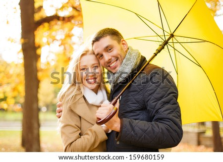 holidays, love, travel, tourism, relationship and dating concept - romantic couple with umbrella in the autumn park - stock photo