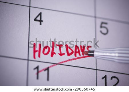 Holidays marked on a calendar - stock photo