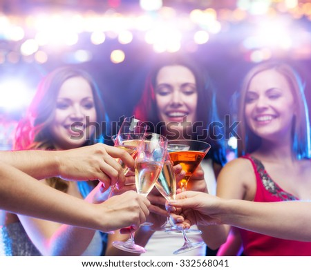 holidays, nightlife, party and people concept - close up of happy friends clinking cocktail and champagne glasses at night club