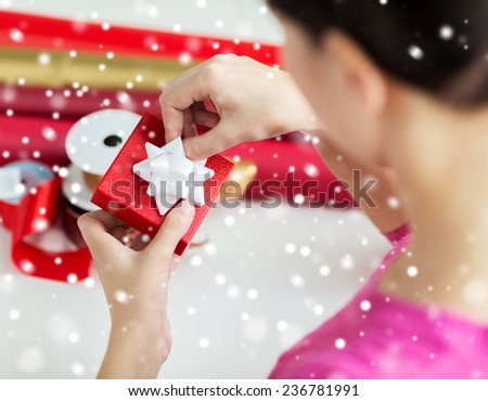 holidays, people and celebration concept - close up of woman decorating christmas present at home - stock photo