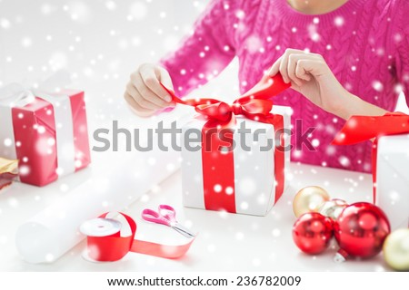 holidays, people and celebration concept - close up of woman decorating christmas presents - stock photo