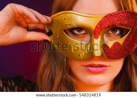 Holidays, people and celebration concept. Closeup woman face with carnival golden red mask on dark background.