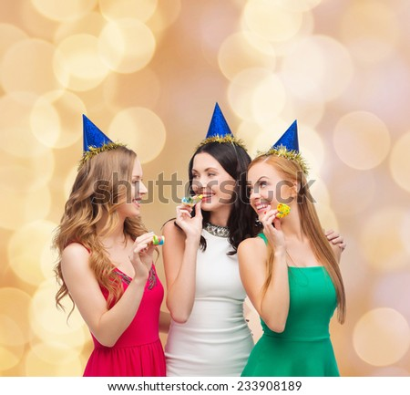 holidays, people and celebration concept - smiling women in party caps blowing to whistles over beige lights background - stock photo