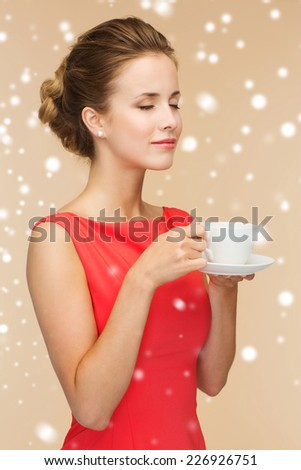 holidays, people and drink concept - smiling woman in red dress with cup of coffee over beige background and snow - stock photo