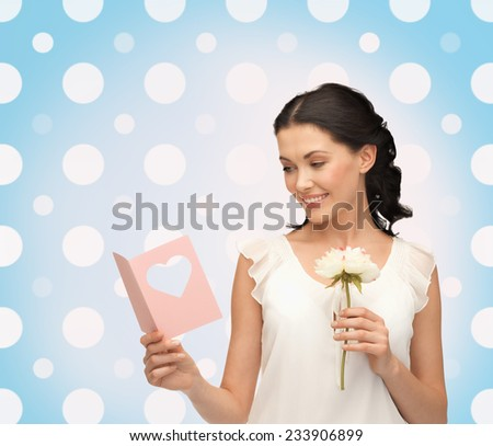 holidays, people and happiness concept - smiling young woman with flower over blue and white polka dots pattern background - stock photo