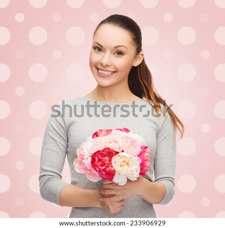 holidays, people and happiness concept - smiling young woman with flower over pink and white polka dots pattern background - stock photo
