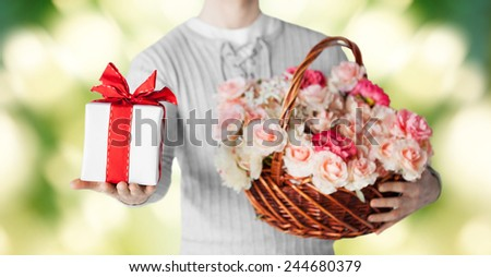 holidays, people, feelings and greetings concept - close up of man holding basket full of flowers and gift box over green background - stock photo